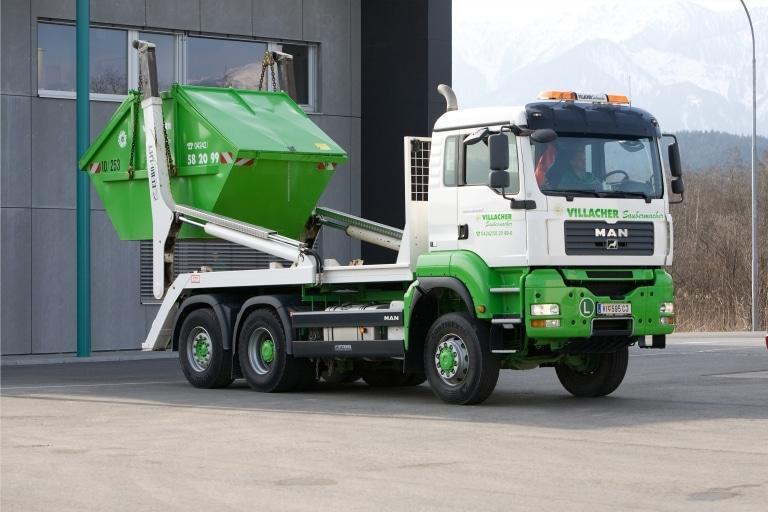 LKW vom Villacher Saubermacher hebt Mulde mit Deckel zum Abtransport an
