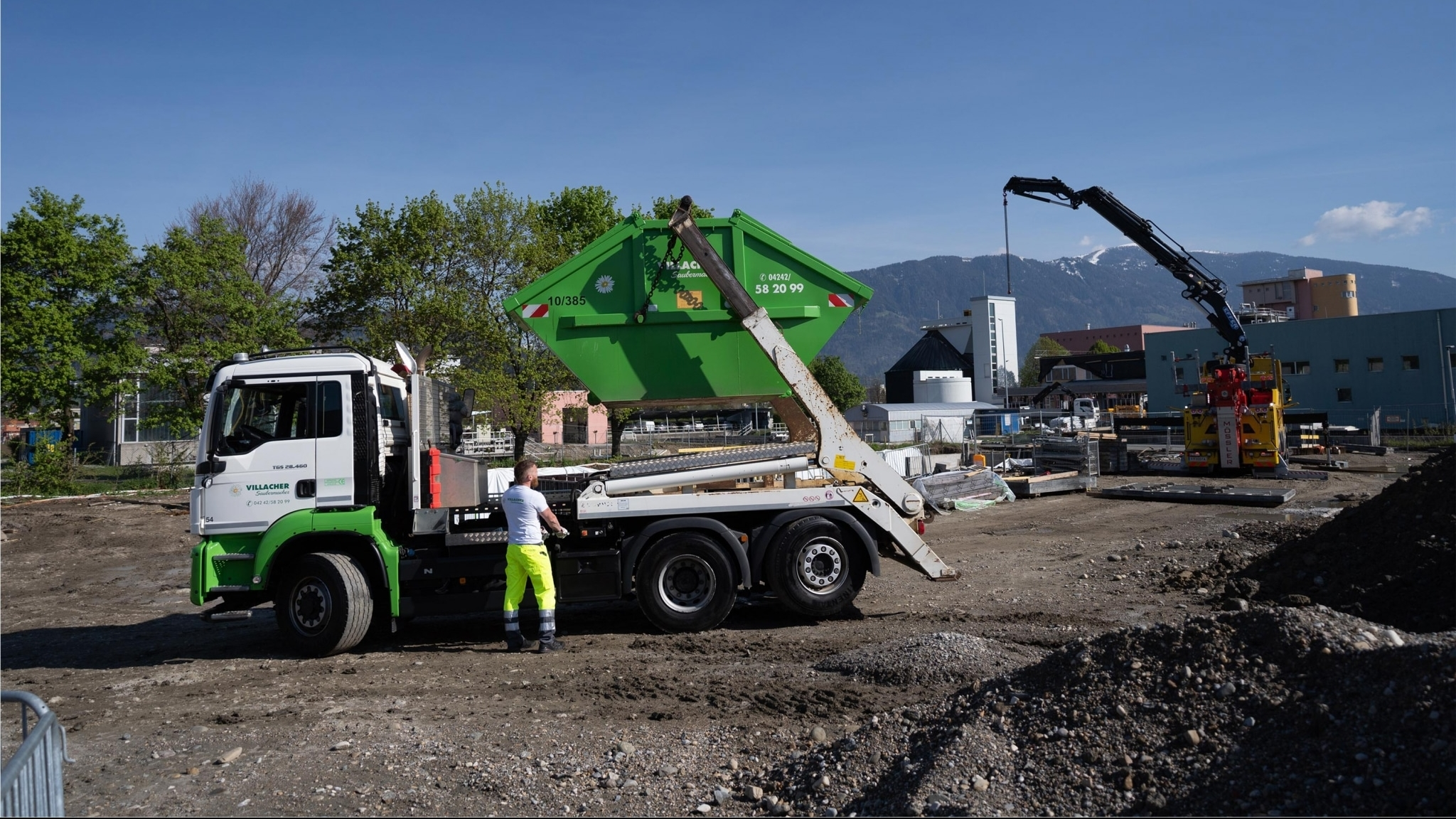 LKW vom Villacher Saubermacher mit Mulde auf einer Baustelle